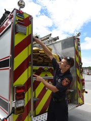 Dave Grundon, a firefighter with the Arlington Fire District, shows where on the truck American flags were hung.
