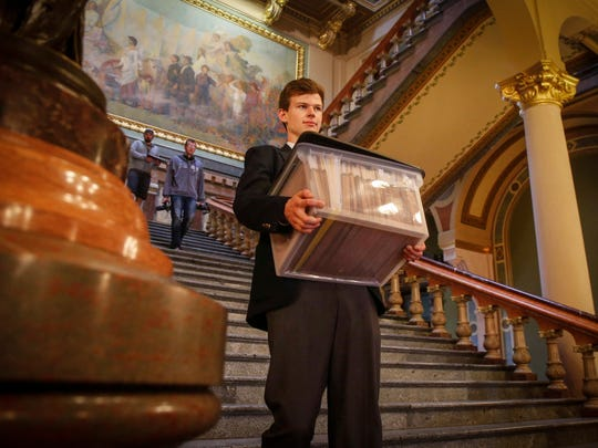 Peyton Parker, 18, of Panora, carries a box of files down from the House chambers on Friday, April 21, 2017, at the Iowa Capitol Building in Des Moines.