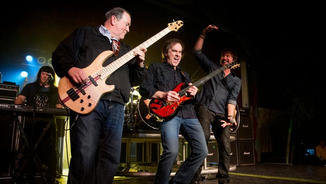 Mike Huckabee plays bass guitar as he performs with the '80s rock band FireHouse at the Surf Ballroom in Clear Lake, Iowa, on Jan. 22, 2016.