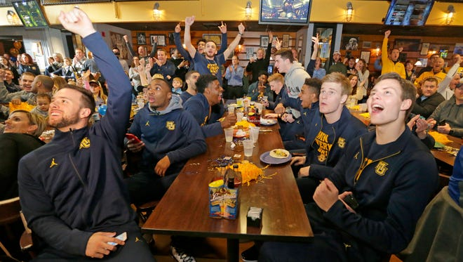 Marquette players celebrate the announcmement of an NCAA bif on Sunday at the Marquette Annex.