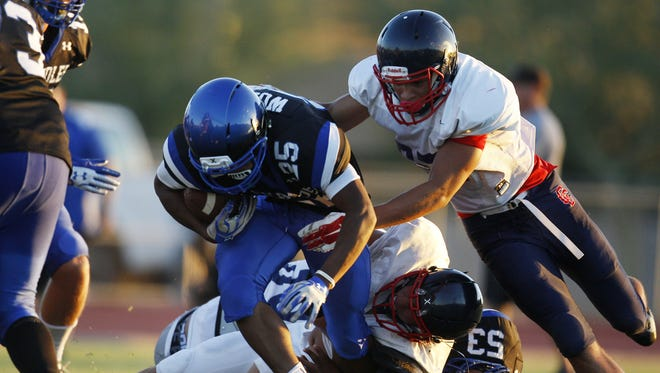 Chandler running back DeCarlos Brooks (25) gets tackled during a scrimmage against Centennial. Centennial High School faced off against Chandler in a preseason scrimmage at Centennial on Tuesday, Aug. 8, 2017.