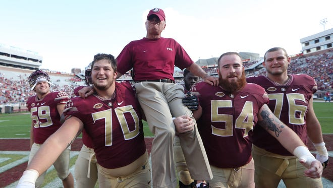 FSU's offensive line, including Cole Minshew (70) and Alec Eberle (54) carry their coach Rick Trickett, as he covers his tears with his hat, after the Seminoles 42-10 win over Louisiana Monroe at Doak Campbell Stadium on Saturday, Dec. 1, 2017.