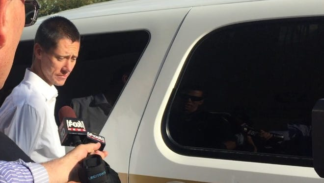 Phoenix police escort Tyler Trammell to a police vehicle after he was taken into custody on suspicion of robbing a bank just feet from a police detective, according to officials.