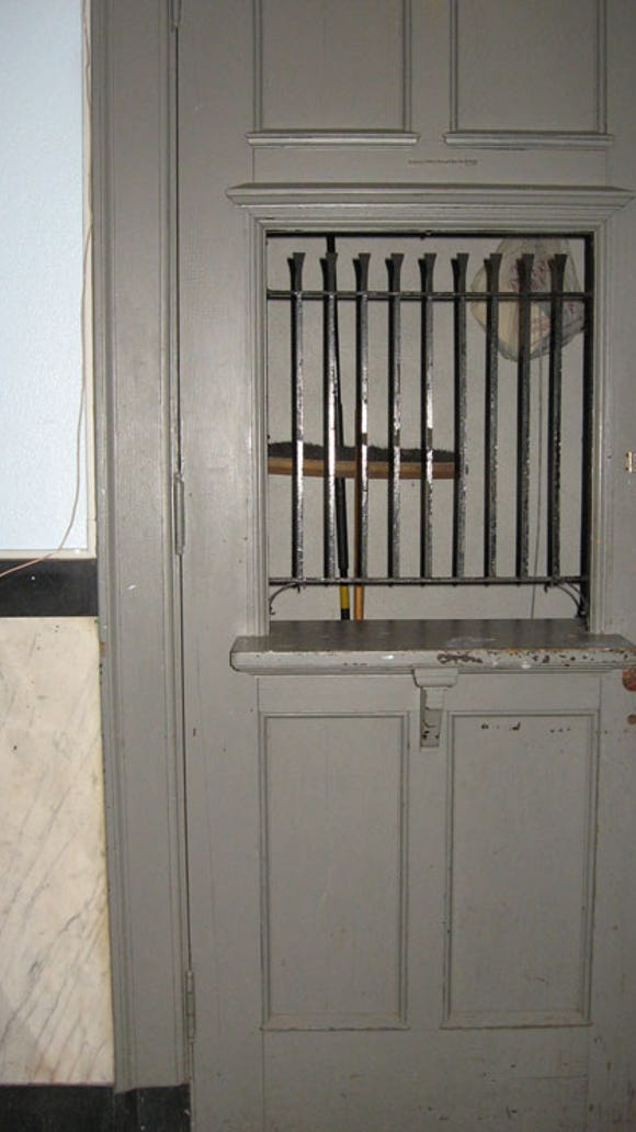 Interior door with barred window and counter, marble wainscot to left