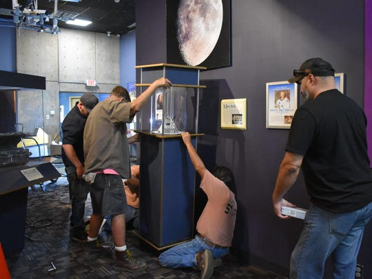 Museum staff and a security team work to reinstall the moon rock exhibit on the fourth floor after the new carpet was installed. The moon rock was brought back to Earth during the Apollo 17 mission by New Mexico Astronaut Harrison Schmitt.  .