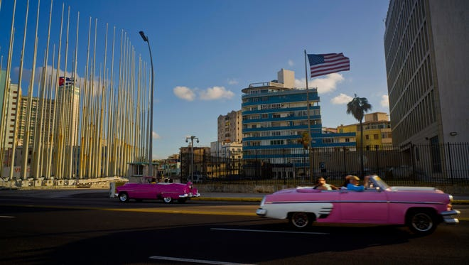 Tourists ride in classic American convertible cars past the United States embassy, right, in Havana, Cuba, Thursday, Jan. 12, 2017. President Barack Obama announced Thursday he is ending a longstanding immigration policy that allows any Cuban who makes it to U.S. soil to stay and become a legal resident. (AP Photo/Ramon Espinosa) ORG XMIT: XRE103