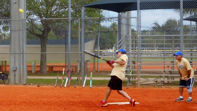 Larry Wickerham blasts a hit as umpire Sal Messina looks on, in this photo from year's past. The Jupiter Senior Softball Association plans to launch its 2018 Winter League soon.