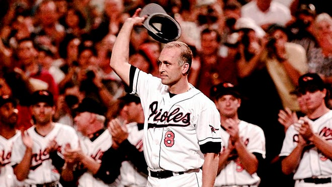 Cal Ripken waves his hat to the crowd as his teammates applaude after breaking Lou Gehrig's consecutive games played record with 2131 games at Camden Yards in Baltimore on Sept. 6, 1995.