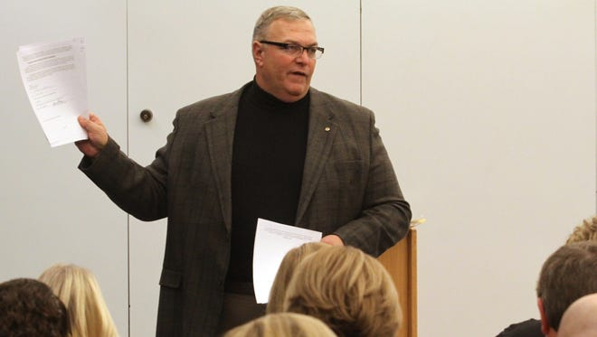 Former Howell Public Schools Superintendent Ron Wilson holds a copy of his contract as he explains issues surrounding his firing at a town hall meeting Tuesday in Howell. The meeting was organized by a group launching a school board recall effort.