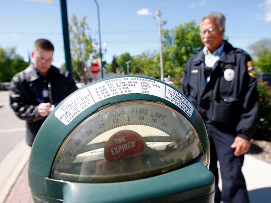 A parking enforcement officer watches as Sycamore, Illinois, Police Department intern in downtown Sycamore.