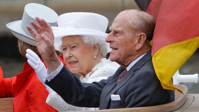 Queen Elizabeth II, center, and Prince Philip, the Duke of Edinburgh wave during a boat tour on the river Spree at the Reichstag building in Germany's capital Berlin, Wednesday, June 24, 2015.