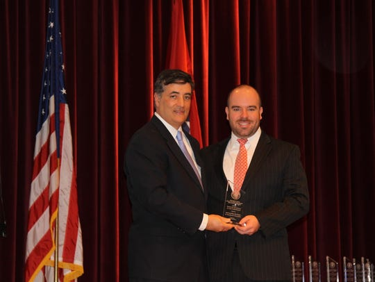 David Rivera, former U.S. attorney, left, presents