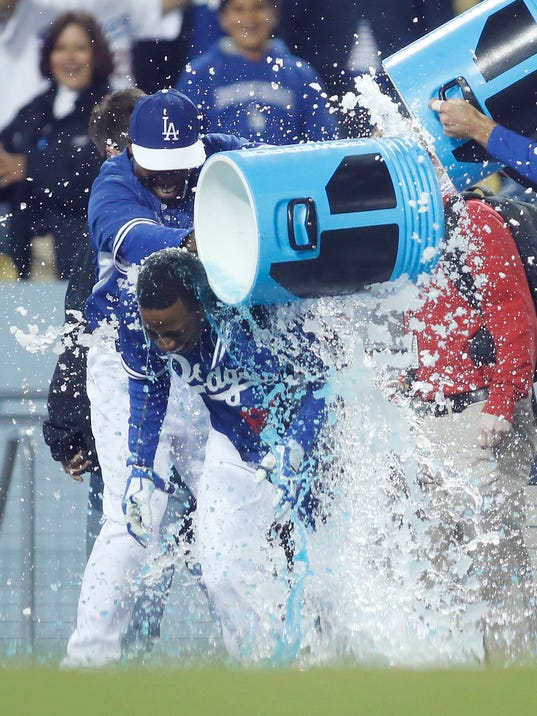 Los Angeles Dodgers' Darnell Sweeney is doused by teammates including Chone Figgins, left, after hitting a walk off single to score Trayvon Robinson against the Los Angeles Angels during the 10th inning of an exhibition baseball game in Los Angeles, Friday, March 28, 2014. The Dodgers won 5-4. (AP Photo/Danny Moloshok)