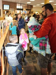 Children wait to flood into the new kids' section at the Marion Public Library. The section opened on Sunday.