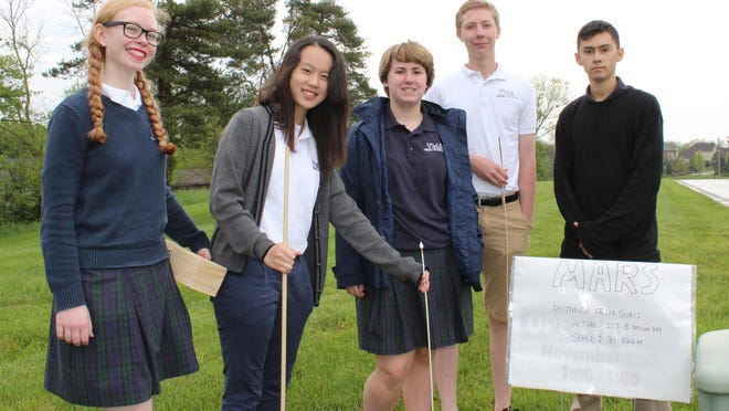 Villa Madonna physics students created a Kentucky scale-distance model of the solar system. They are junior Eileen Bunch, sophomore Mina Kang of Hebron, senior Mary Wurtz of Crestview Hills, junior Will Leverman of Erlanger, and junior Vincent Steinman of Independence.
