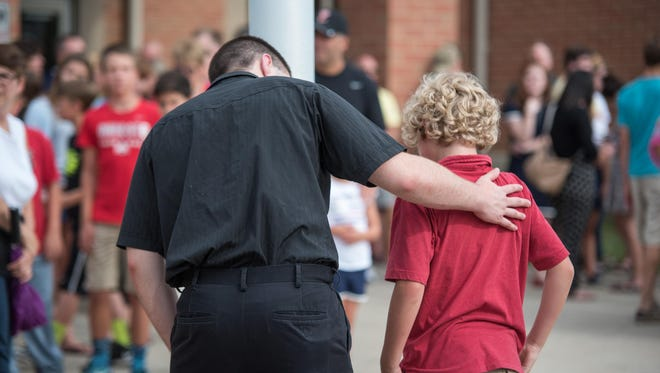 Pedro Del Moral Lopez, 19, consoles Saul Flick, 10, at Sonny Kim's vigil outside of Loveland Middle School on June 20.