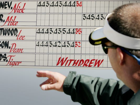 FILE - In this Feb. 18, 2006, file photo, PGA Tour scoreboard calligrapher Ray Stansberry points to the official scoreboard notation that Tiger Woods had withdrawn before the third round of the Nissan Open golf tournament at Riviera Country Club in Los Angeles. Woods is playing at Riviera this week for the first time in 12 years. (AP Photo/Reed Saxon, File)