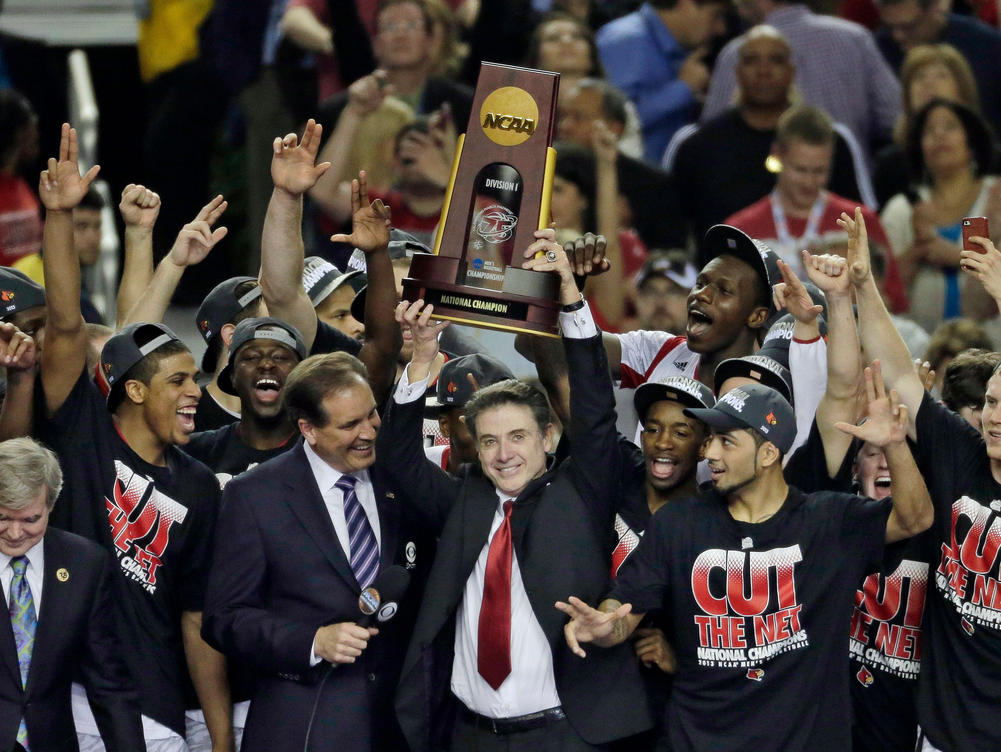 In this April 8, 2013, file photo, Louisville players and head coach Rick Pitino celebrate after defeating Michigan 82-76 in the championship of the Final Four in the NCAA college basketball tournament in Atlanta. Louisville announced Wednesday, Sept. 27, 2017, that they have placed basketball coach Rick Pitino and athletic director Tom Jurich on administrative leave amid an FBI probe.