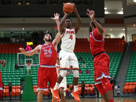FAMU's Elijah Mayes shoots a jumper, spliting two Delaware State defenders at the Al Lawson Center on Monday, Jan. 15, 2018.