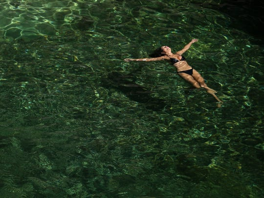 A woman floats at Three Pools Recreation Area in the