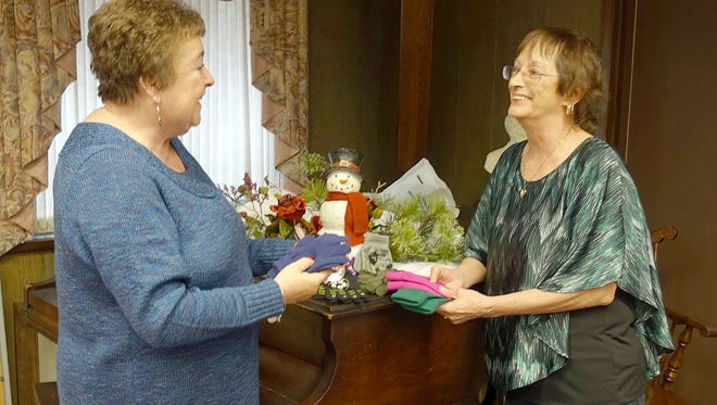 Norene Ritter (left), president of the Woman's Club of Vineland, and club member Alberta Kidd count winter accessories collected at the January meeting for the St. Vincent DePaul food pantry and clothes closet.