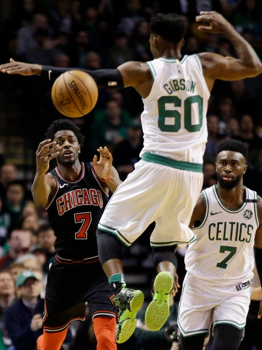 Chicago Bulls guard Justin Holiday, left, passes the ball upcourt past Boston Celtics Jonathan Gibson (60) as Celtics guard Jaylen Brown, right, watches in the second half of an NBA basketball game, Friday, April 6, 2018, in Boston. (AP Photo/Elise Amendola)