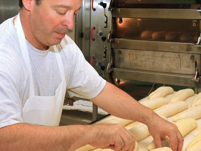 Rob DeMarco of Red Bank uses a lame to score loaves of Italian bread before they are loaded into the oven at Demarco's in Matawan.