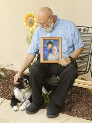 Tom Fister holds a portrait of himself and his wife Sue Fister as he sits with his dog Shamor at his home Thursday, Sept. 3, 2020 in Copley, Ohio. Fister recently ended up in the ER with a heart issue while he was caring for his wife who is currently being hospitalized with health issues.