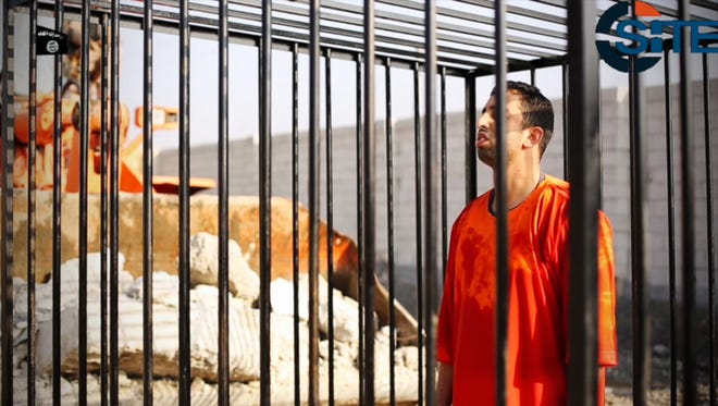 This still image from a video released by the Islamic State and posted on the website of the SITE Intelligence Group on Feb. 3, 2015, purportedly shows Jordanian pilot Lt. Muath al-Kaseasbeh standing in a cage just before being burned to death by his captors.