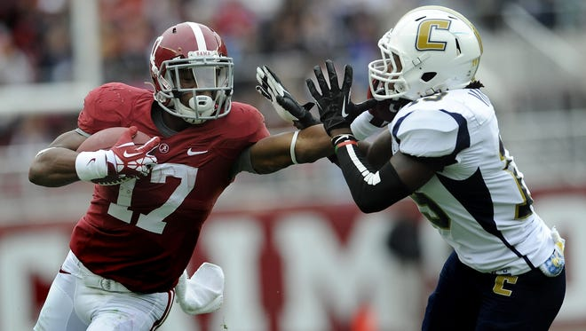 Alabama running back Kenyan Drake (17) stiff arms University of Tennessee Chattanooga defensive back Dee Virgin (19) at Bryant Denny Stadium in Tuscaloosa, Ala. on Saturday November 23, 2013.