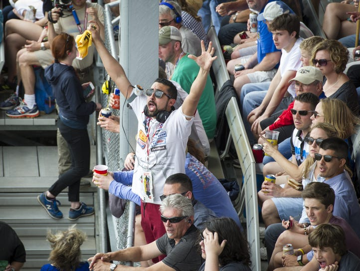 A fan reacts as he watches a pass on the track during