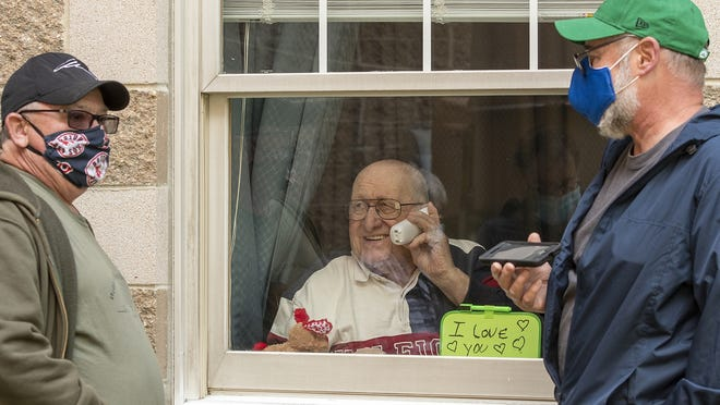 Joseph Fluet, left, and his brother Chuck Fluet, right, use phones as they visit with their father, Raymond Fluet, through a window at Holy Trinity Nursing Home in Worcester on Monday.