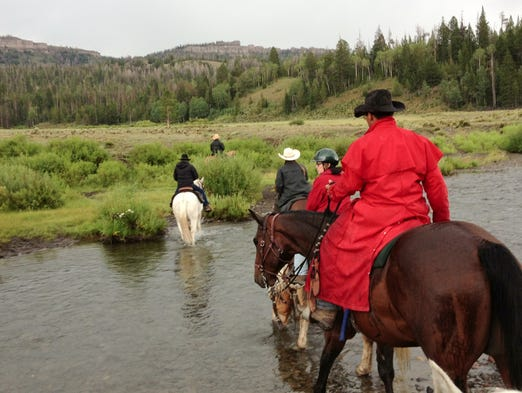 Wrangler Dallin Maples, 25, herds guests across Horse Creek at T-Cross Ranch, outside Dubois, Wyo.