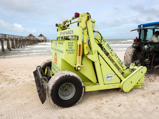 A city of Naples tractor cleans up dead fish littering the beach near the Naples Pier on Friday, Oct. 7, 2016. Naples officials attributed the large fish kill to a combination of red tide and local effects of Hurricane Matthew.