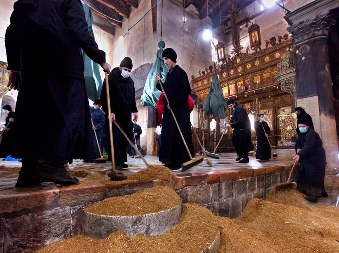 Greek Orthodox clergy sweep up saw dust on Dec. 31 from the nave area in the Greek Orthodox area of the Church of the Nativity in the West Bank town of Bethlehem. The church is considered by many to be the birthplace of Jesus Christ.  Several religions are working together to fix up the church.