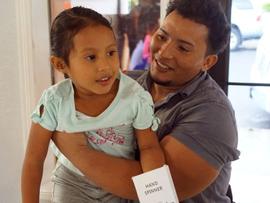 Jose Rodrigo Urbina, 25, holds his daughter, Nathaly