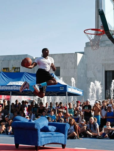 Dustin Jones leaps over a love seat in the finals of the slam dunk competition during Hoopla on Saturday, Aug.2, 2014. Jones won the competition.