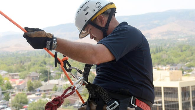 A firefighter slowly climbs over the ledge of the eight floor of the Reno Justice Court as part of a rappelling exercise Thursday in downtown Reno. The rappelling practice was part of the first Regional Safety and Emergency Preparedness Expo held in Wingfield Park.