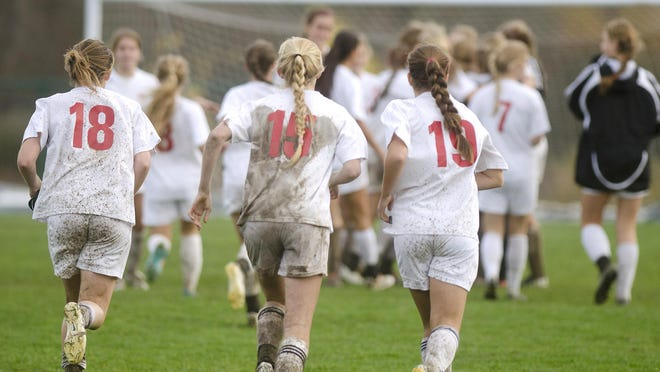 Champlain Valley's Megan Gannon (18), Sierra Morton (15) and Naomi Burhans run to celebrate with their team after the Redhawks 3-0 win over Colchester in the Division I girls soccer semifinals on Tuesday.