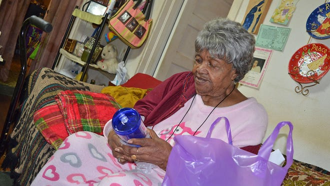 Alberta Mullen opens Christmas gifts she received along with a hot meal as part of Stewpot Ministries' Meals on Wheels program.