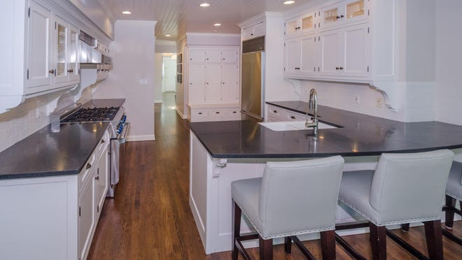 In the kitchen, crisp white cabinetry is accented by dark honed granite countertops and a subway tile backsplash. Top-of-the-line appliances make it a chef's dream.