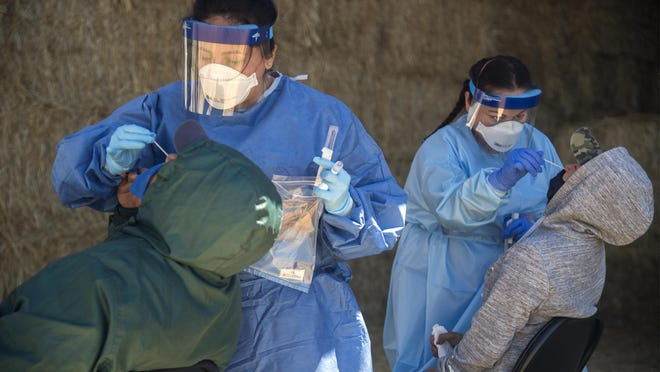 LVN Isabel Quintero, left, and RN Katrina Nguyen swab farmworkers during COVID-19 testing at a farm in Linden.