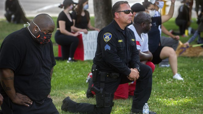 Stockton Police Sgt. Gary Benevides takes a knee with others during a protest on June 1 at Dr. Martin Luther King Jr. Plaza. Demonstrators  protested the death of George Floyd while in the custody of Minnesota police.