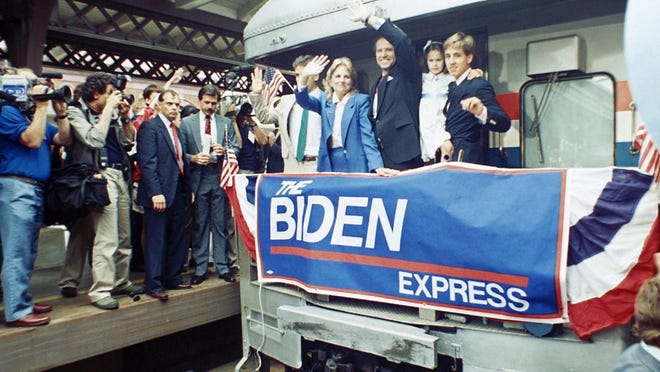 Sen. Joe Biden (D-Del.) waves from his train as he leaves Wilmington, Del., after announcing his candidacy for president, June 9, 1987. At right, son Beau carries daughter; to Biden's right is his wife Jill and son Hunt.