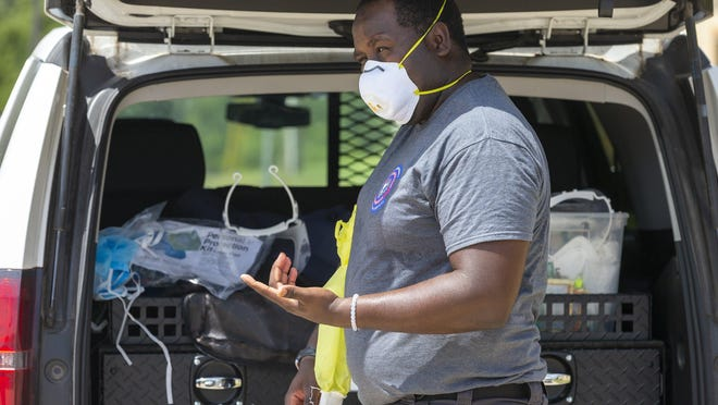 Mental health specialist Ricco Williams demonstrates wearing high risk PPE, generally used for work inside a home, at a Round Rock fire station in July. The Mobile Outreach Team has provided treatment options to people in crises and diverted patients away from jail, hospital emergency departments and state hospitals.