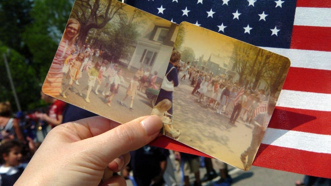 During the Huntington Elementary School Memorial Day Parade on May 27, 2011, Gini Duggan of Bridgewater shows photographs of the 1972 Huntington School Parade, which she was in.