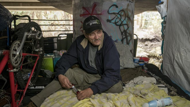 David Higgs is shown in February sitting on his blanket at a homeless camp under East Anderson Lane near Cameron Road. Higgs said he has been homeless since he was released from prison in 2013.