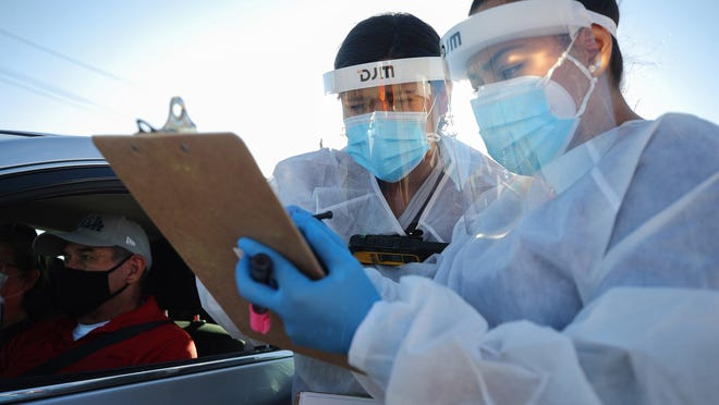 Health care workers check information at a COVID-19 testing site in El Paso this month.