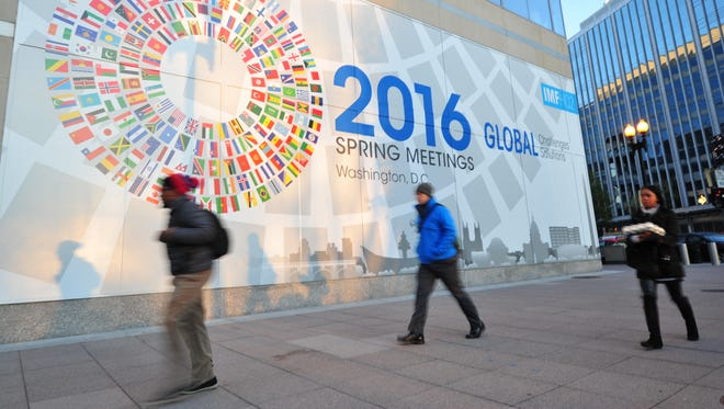 People walk past a mural advertising the World Bank-IMF 2016 Spring Meetings in Washington on April 5, 2016. This year's events will run April 12-17, 2016. Thousands of government officials, journalists, civil society organizations, and participants from the academic and private sectors.