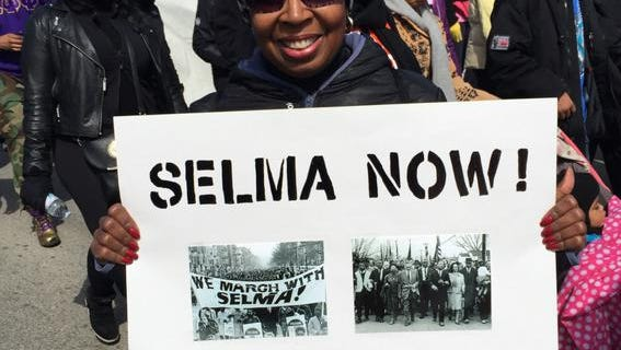 Re'Nita O'Bannon of Indianapolis, a participant in the local march to remember Selma on Saturday, March 7, 2015, held up a sign she made to commemorate the historic event. About 650 marchers walked on a 5-mile route from Light of the World Christian Church on the Northwestside to Downtown to gather at the Indiana Statehouse.